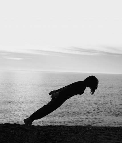 grey person doing gravity lean on the shore black-and-white