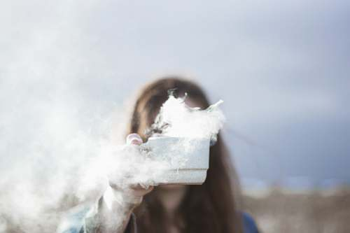 food person holding white ceramic cup with smoke flowing inside teacup