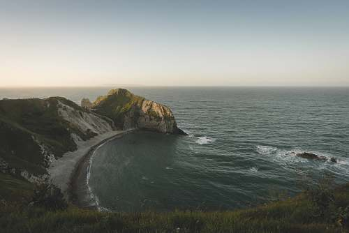 cliff aerial photography of green body of water and mountain united kingdom