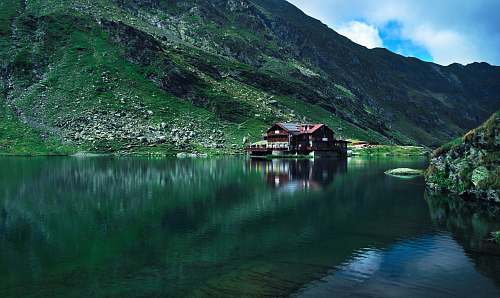 building brown wooden house near mountain surrounded with water at daytime boat
