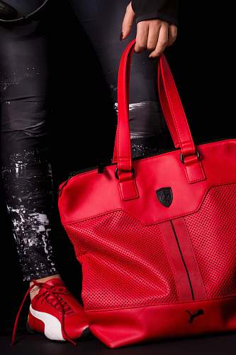 accessory person holding red Puma leather tote bag bag