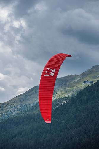gliding person riding red parachute at daytime leisure activities