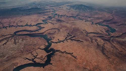 landscape aerial photo of brown mountains and river river