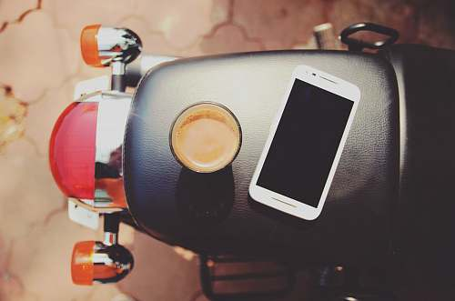 phone white smartphone on black leather motorcycle seat coffee