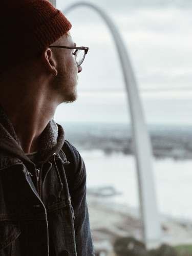 clothing man in denim jacket standing beside window looking outside jacket