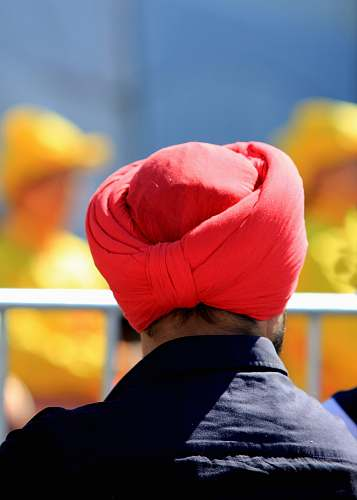 clothing man with red turban facing back near railings turban