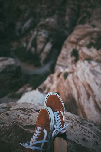 clothing person sitting on cliff wearing brown-and-white Vans low-top sneakers footwear