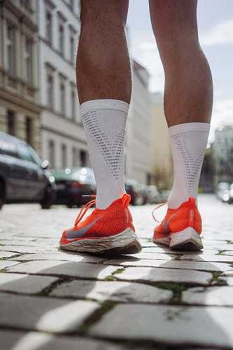 clothing person wearing orange Nike running shoes standing on pavement shoe