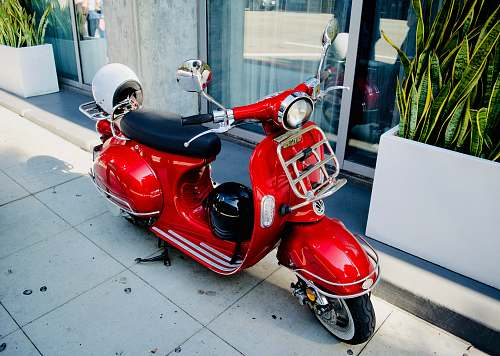 clothing red motor scooter parked near glass door helmet