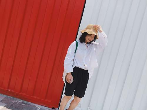 clothing smiling woman standing beside red and white wall human