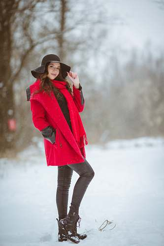 clothing woman in red coat wearing black sunhat smiling while standing on snow-covered ground during daytime coat