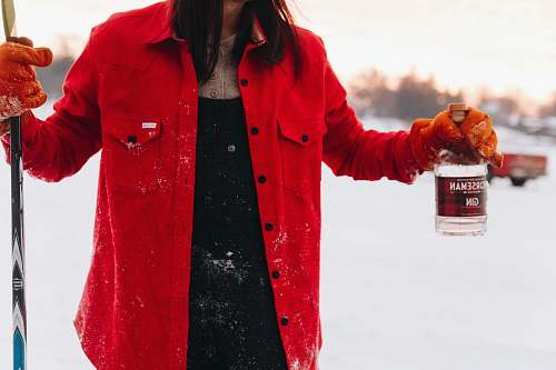 clothing woman in red jacket holding gin bottle coat