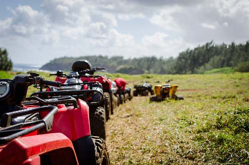 transportation focus photography of ATV's falling in line on grass field vehicle