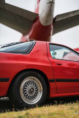car red coupe under an airplane transportation
