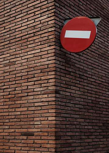 brick red and white signage on red brick wall at daytime wall