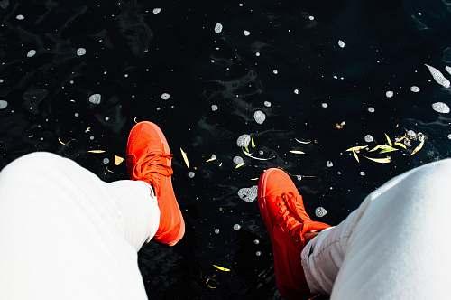 legs person wearing orange sneakers sitting near water shoes