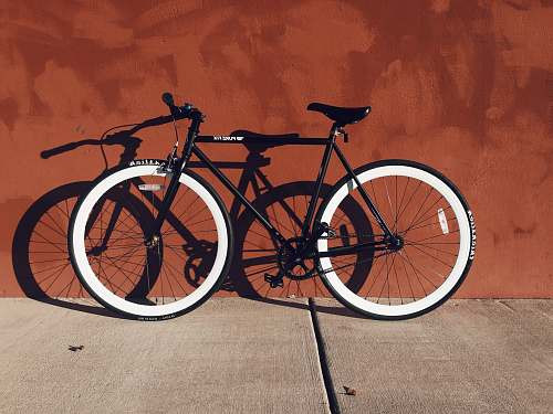 photo bike black and white mountain bicycle near brown wall red wall free for commercial use images