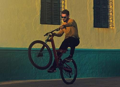 bike man riding bicycle doing tricks near building photography man