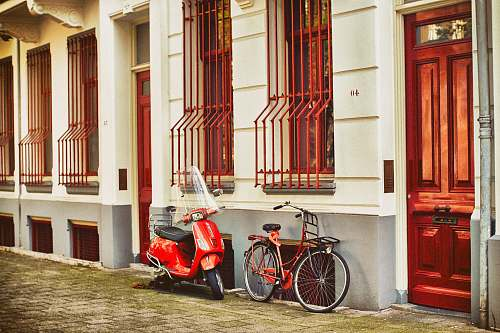 door red motor scooter parked beside house bicycle