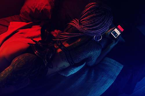 red woman lying on bed holding smartphone light