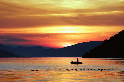 sunset silhouette photography of person standing on boat fishing