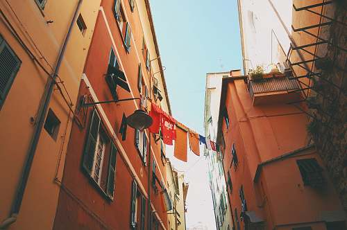 city assorted-color textiles hanged on clothes dryer in between houses italy