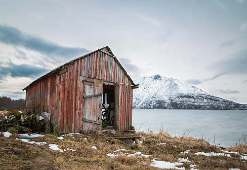 hut landscape photography of brown wooden shed near ocean water and snow-coated mountains during daytime rural