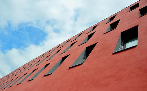 windows low-angle photography of red concrete building perspective