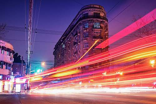 city time-lapse photography of cars passing through the road between buildings during night time urban