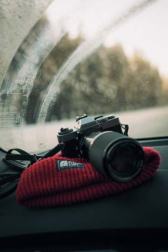 lens photo of gray Minolta DSLR camera on glove compartment minolta