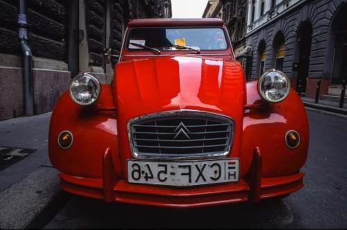 light red Citroen car parked on road headlight