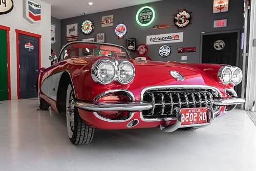 classic red coupe inside gray garage vintage