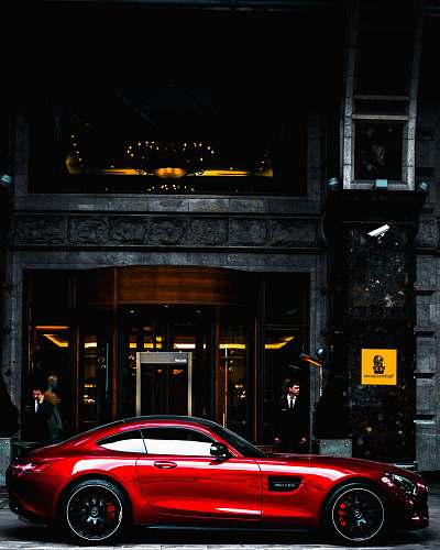 automobile red coupe parked in front of black and gray building during daytime transportation