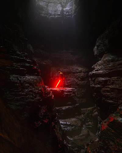 hole person holding red lightsaber nature