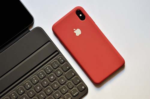 electronics space gray iPhone with red case beside tablet keyboard mobile phone