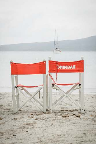 yacht two white folding chairs during daytime at beach boat