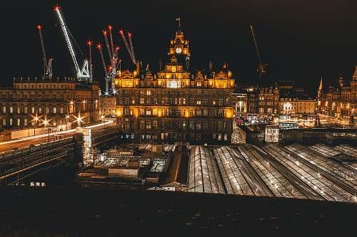 edinburgh city with fireworks display during nighttime construction crane