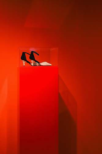 apparel black-and-brown ankle-strap heeled sandals on red and clear glass display counter footwear