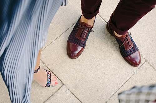 shoe woman standing near man on beige tiled floor footwear