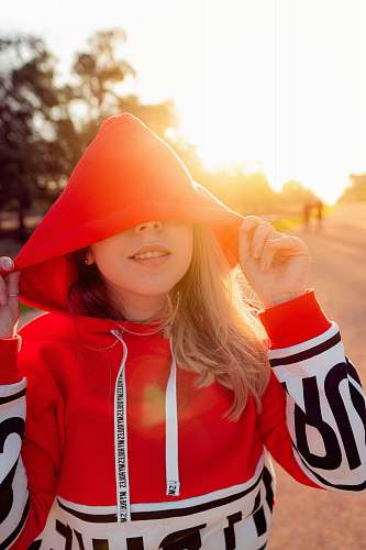 apparel woman wearing red and white pullover hoodie during sunrise hood