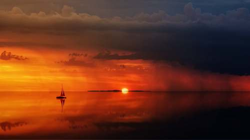 sky silhouette of sailboat on body of water sunrise