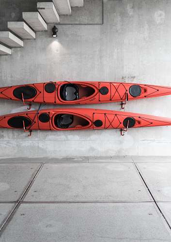denmark two red kayaks hanging on wall under stairs wall