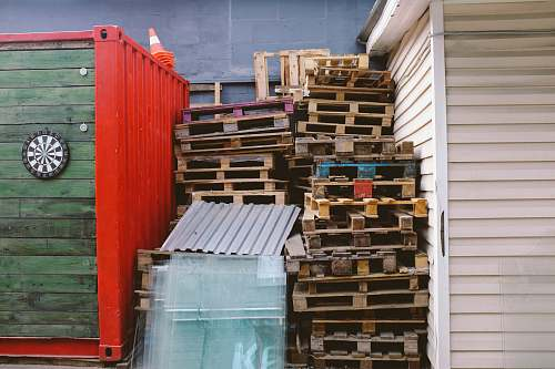 pallets brown wooden crate lot between red and green shipment container pallet