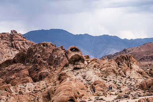 alabama hills brown rock formation near mountain under cloudy sky nature