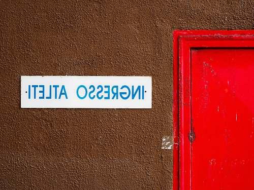 italy close-up photo of Ingresso Atleti signage beside door wall
