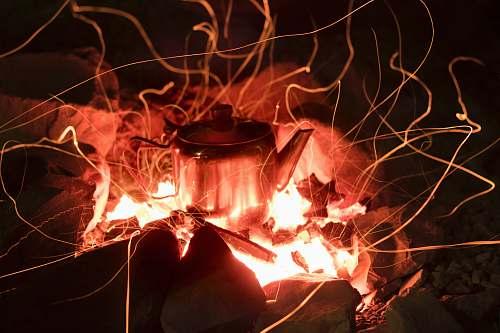 orange gray stainless steel kettle on fire pit light