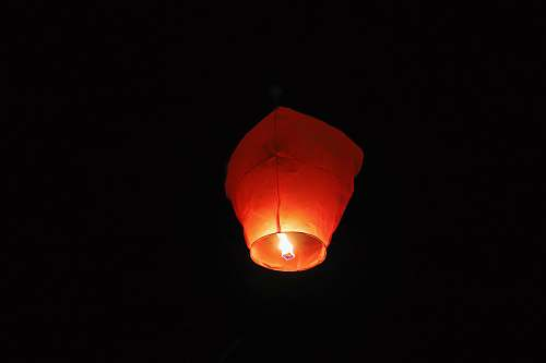 candle paper lantern with lighted candle in dark room lantern