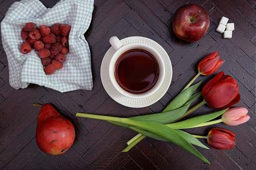 fruit teacup on saucer near apple and tulip flower drink
