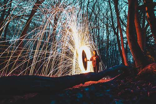 sparks woman in the middle of forest steelwool photo night
