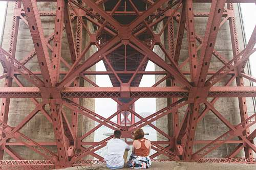 san francisco man and woman sitting near red metal scaffolding during daytime underneath